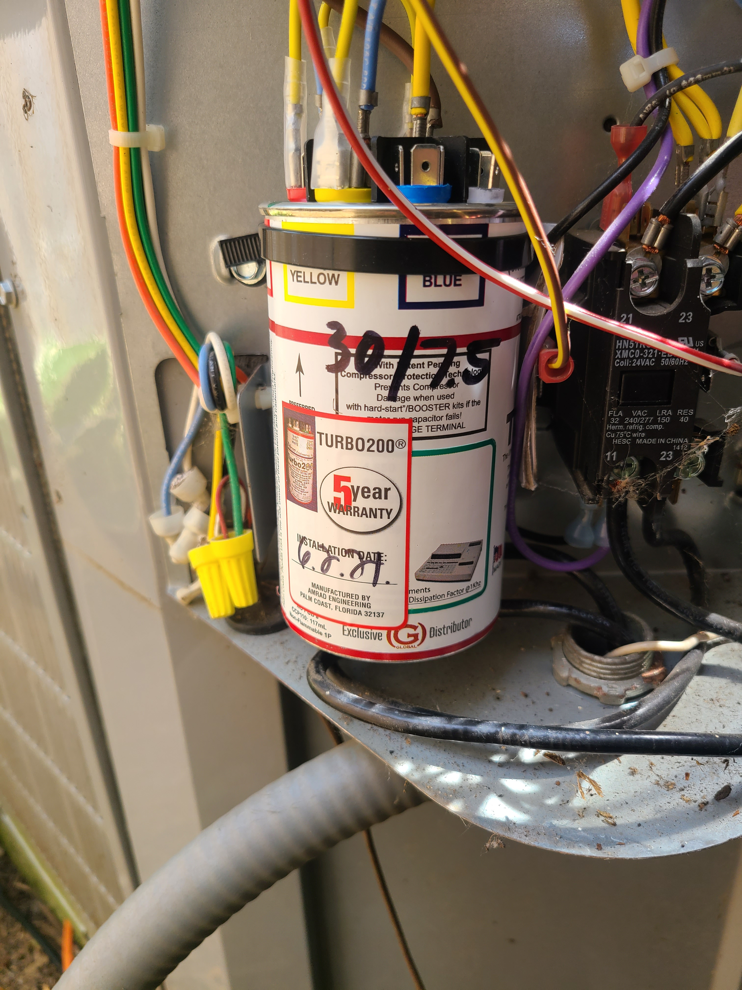 Replacing a low reading dual capacitor in a Carrier air conditioner.
